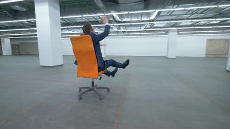 saadet : Man in a suit is fooling around while sitting in a rolling chair Stok Video