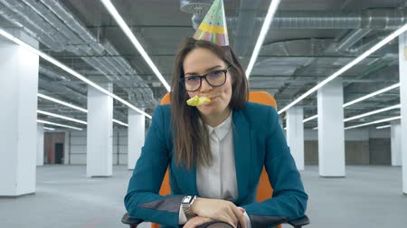 infeliz : Empty hall with a tired woman in office suit and a birthday hat Stock Footage