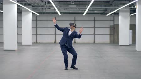 utánzás : Businessman in VR-glasses is walking around an empty hall Stock mozgókép