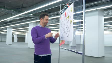 good looking guy : Male architect is observing layouts on a plastic board with a smile