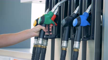 filling station : Green gas nozzle is getting put back into its place by a man. Gasoline, gas, fuel, petroleum concept. Stock Footage
