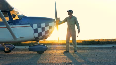 hull : Pilot cleans airplanes propeller, side view.