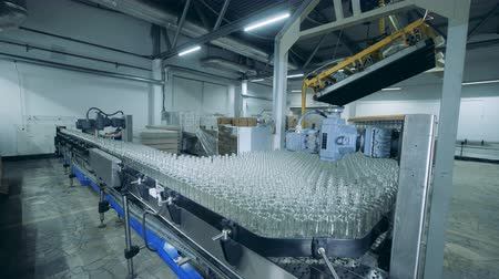 wódka : Automated conveyor moving bottles in facility at alcohol plant.