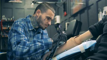 challenged : Male artist is drawing a tattoo on an artificial hand Stock Footage
