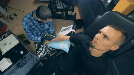 utánzás : Man with a synthetic arm is getting a tattoo