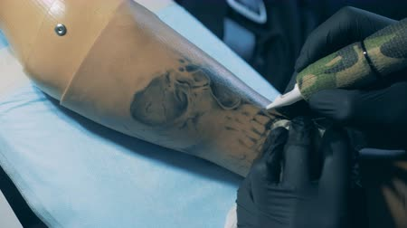 desvantagem : Close up of a black-ink tattoo getting done on a synthetic hand