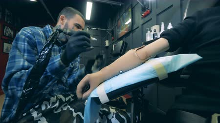 končetina : Male artist is doing a tattoo on a synthetic arm in his studio