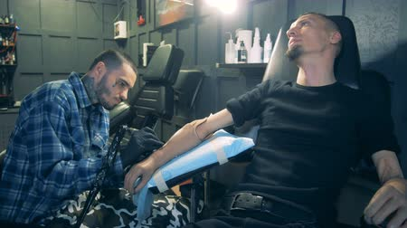 challenged : Tattoo salon with a disabled man getting a tattoo on his prosthesis