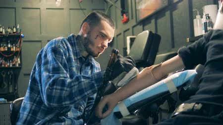 physically : Workshop with a male artist tattooing a prosthetic arm Stock Footage