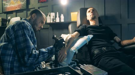 physically : A man with artificial hand is getting a tattoo Stock Footage