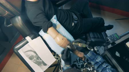 physically : View from above of male prosthetic arm getting tattooed Stock Footage