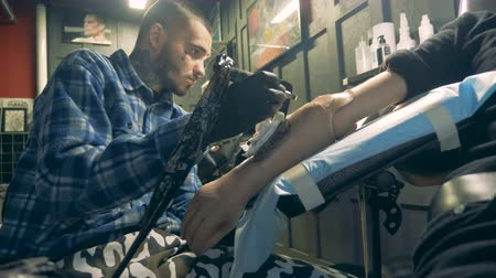 physically : Male artist is tattooing a synthetic hand and wiping it Stock Footage