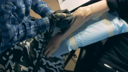 робот : Top view of a black-coloured tattoo getting drawn on a synthetic arm