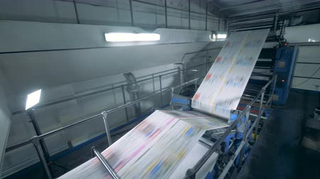 jornal : A conveyor moves sheets at a printing office, close up. Vídeos