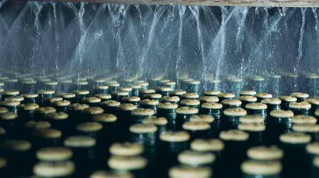 scellé : Sealed bottles sprayed with water, automated machine.