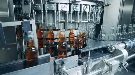 скотч : Whiskey, scotch, bourbon production. Process of bottles filling with liquor at alcohol factory, automated machine. Стоковые видеозаписи
