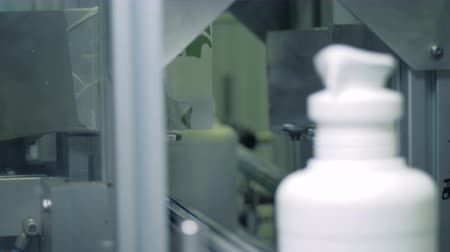 conveyor belt : Automated machine cuts lids of plastic containers on a conveyor. Stock Footage