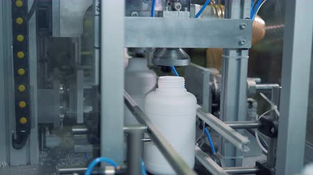 sterilità : A machine presses white bottles while they move on a line, modern production.