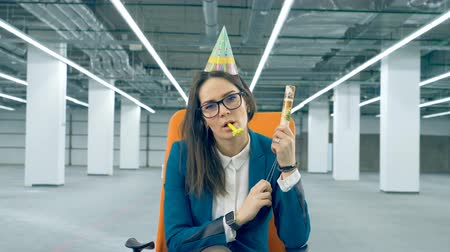 apito : Female clerk explodes a party cracker, wearing a celebration cap. Dull birthday concept.