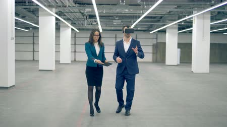 área de trabalho : A man wears VR glasses while working with a businesswoman, modern technology. Stock Footage