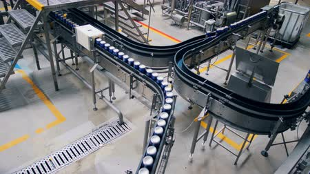 wort : Beer cans moving on a conveyor, top view.