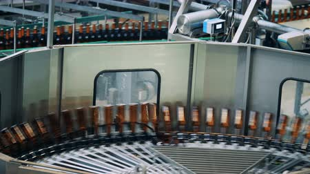 fermenting : Bottles with beer rotating on a circle conveyor, top view.