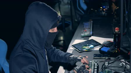 inbraak : Side view of a disguised hacker working on the computer