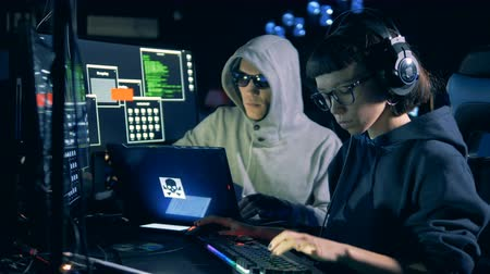 skillful : Male hacker is assisting to a female one while working Stock Footage