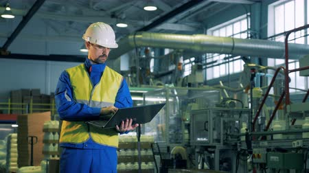 energetyka : Plant unit producing chemicals with a male worker operating a laptop Wideo