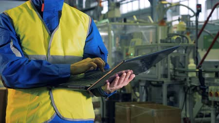 polymers : Laptop in the hands of a man working in a factory Stock Footage