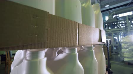 onto : Carton boxes with plastic vessels are getting stacked together