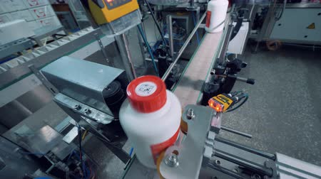 eenheid : Plastic bottles with chemicals are getting polished by a machine