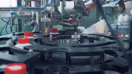 polymers : Round conveyor moving plastic bottles with their caps getting screwed Stock Footage