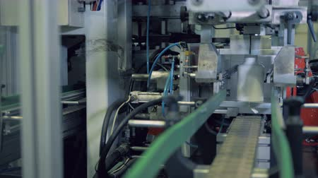 slashing : Factory machine is shaping plastic bottles and cutting them off Stock Footage