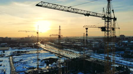 emel : Tower cranes working on a site near a road on a sunset background. Stock mozgókép
