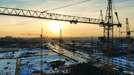 kusy : Construction site with working cranes near a road. Dostupné videozáznamy