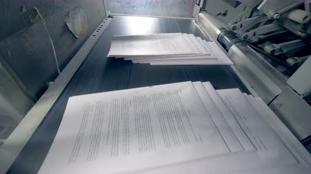 パブリッシュ : Piles of paper get onto a conveyor, close up.