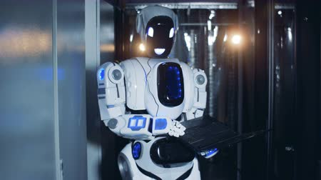андроид : Human-like robot is standing with a laptop in a server room