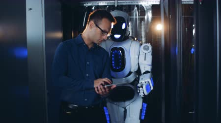 vezetett : Human-like droid is being guided by a walking male expert