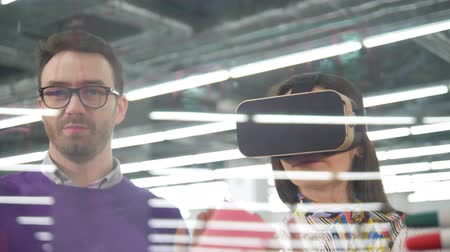 área de trabalho : A female architect wears VR glasses while working with a blueprint, while a man talks. Stock Footage