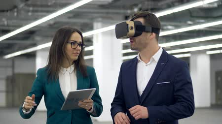 realidade : Male realtor in VR glasses talks to a woman with tablet in hands.