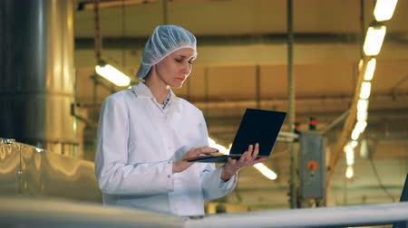 lab employee : Factory facility with a lady specialist operating a laptop
