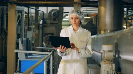 construtor : A lady in uniform with a laptop is walking along the plant Stock Footage