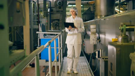 инспектор : Woman in workwear is walking across the factory with a laptop