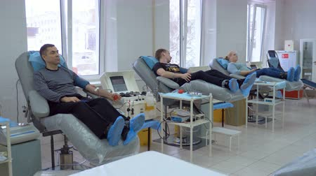 mechanically : Donors are lying in armchairs and giving blood