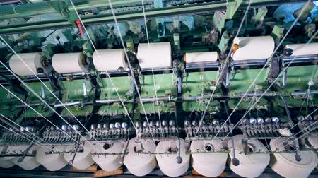 poliester : White clews spinning on modern machines at a textile factory.