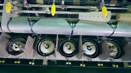 шить : Coiling equipment works with white fiber at a textile factory.