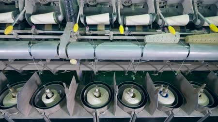 automatický : Textile factory equipment coils white fiber onto spools automatically.