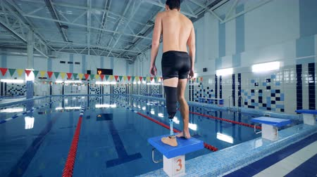 končetina : Man with artificial leg stands near a pool while training.