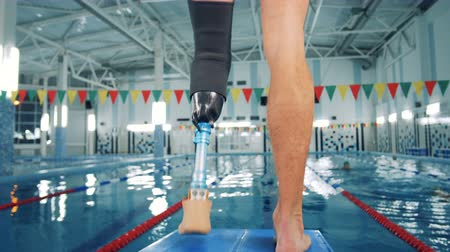 prosthesis : Swimmer with a leg prosthesis training near a pool, bionic equipment.